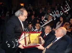 يحيي عاشور يقدم درع المركز الي الدكتور حسن حلمي
