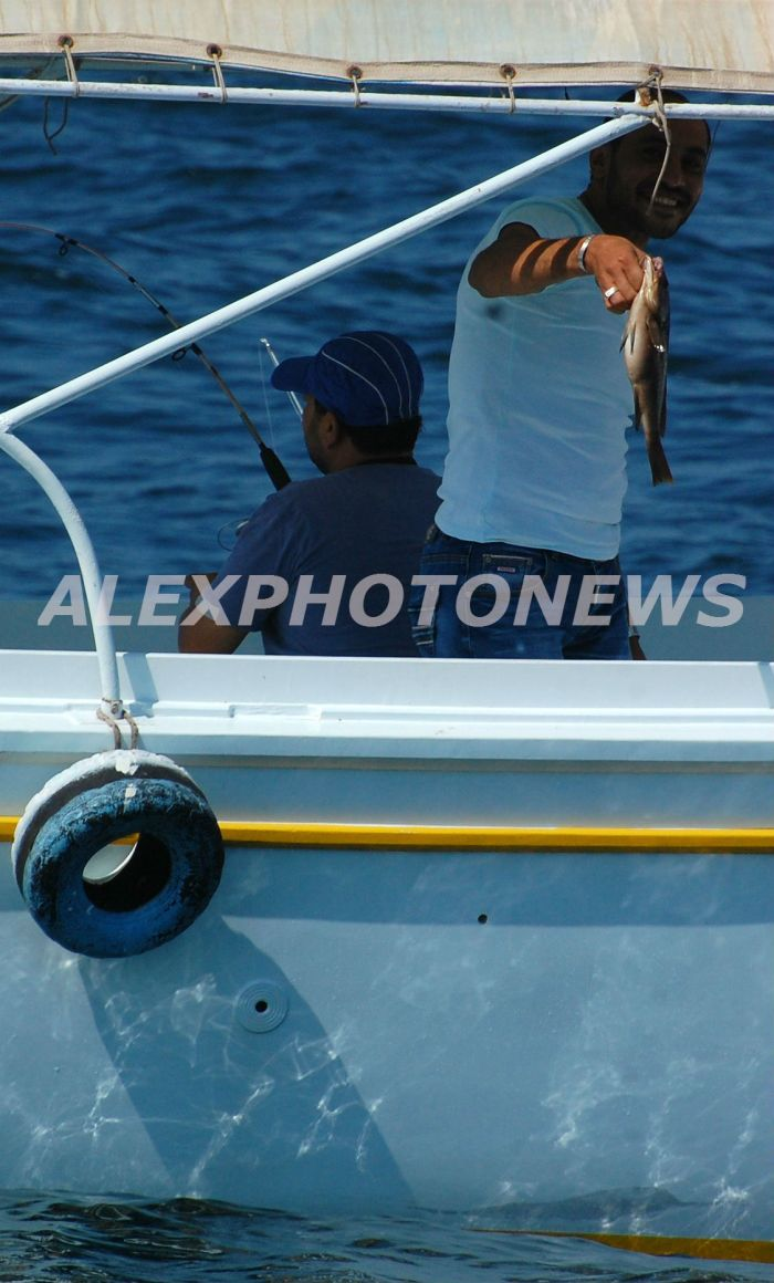 احد المشاركين في المسابقة يرفع احد الاسماك التي قام بصيدها - تصوير ترتيل طارق